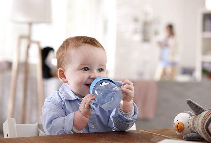 Малыш пьет воду из поильника
