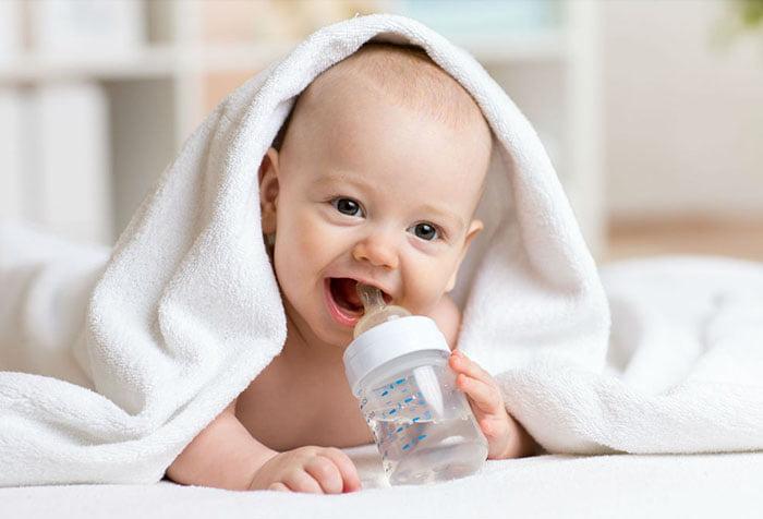 Малыш держит бутылочку с водой