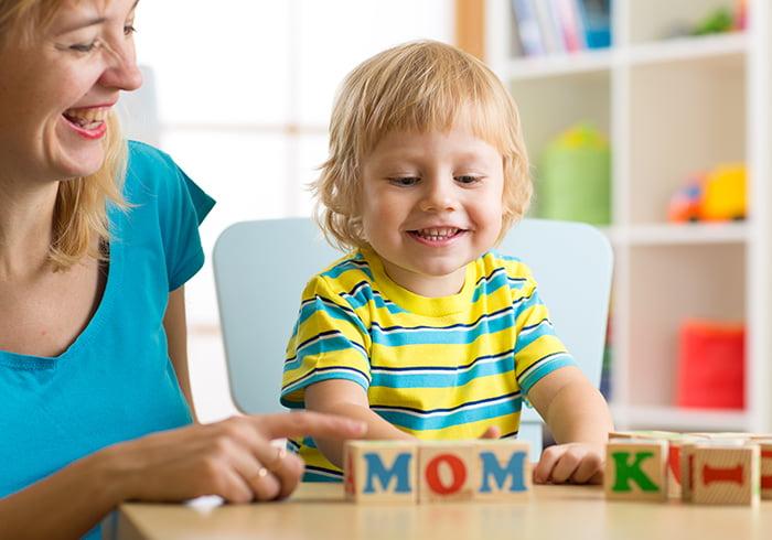 Ребенок играет в кубики с английскими буквами