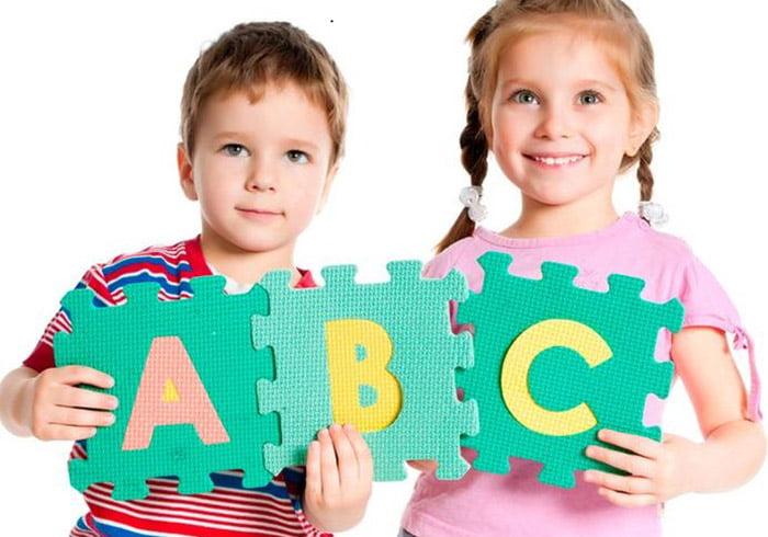 Дети держат пазлы с английскими буквами