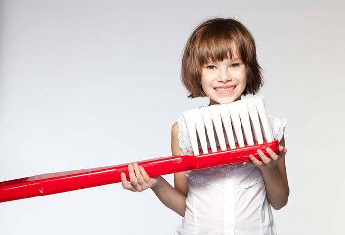 Девочка с большой зубной щеткой