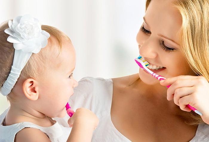 Маленькая девочка учится чистить зубки
