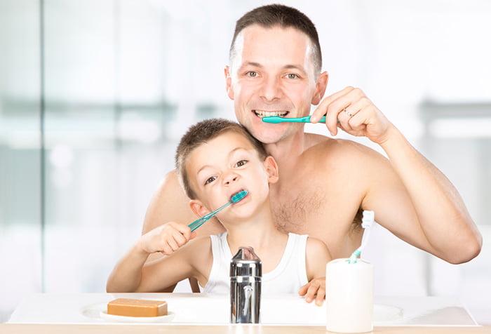 Мальчик с папой чистят зубы