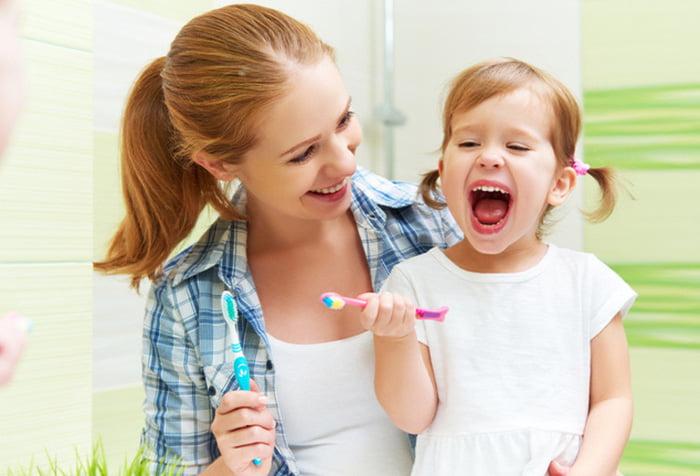 Девочка с мамой чистят зубы