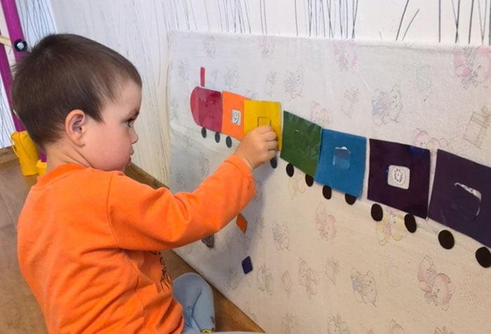 Ребенок клеит цветной паровозик
