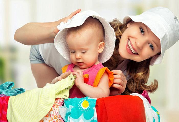 Мама примеряет одежду малышке