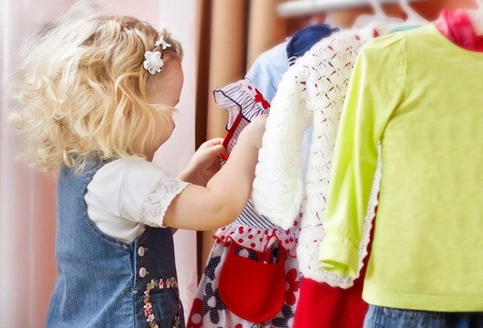 Маленькая девочка выбирает одежду