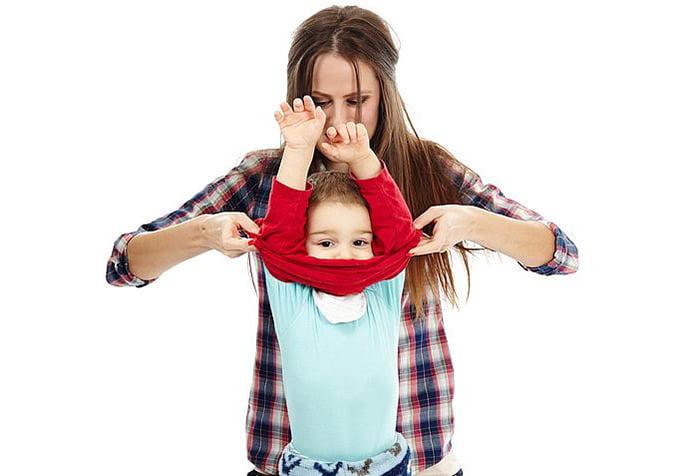 Мама помогает ребенку надеть свитер