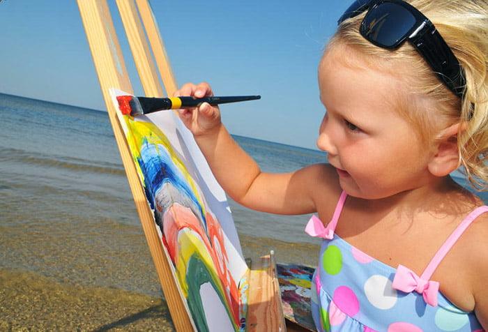 Девочка рисует радугу на берегу моря