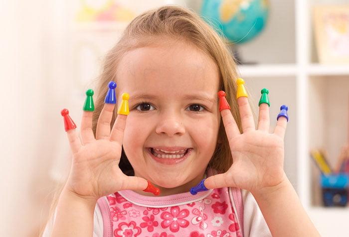 Девочка надела колпачки на пальцы