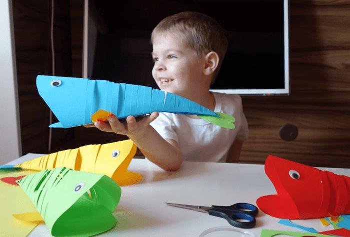 Ребенок вырезает китов из цветной бумаги