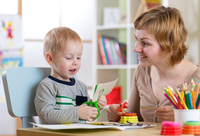 Мама учит ребенка вырезать ножницами
