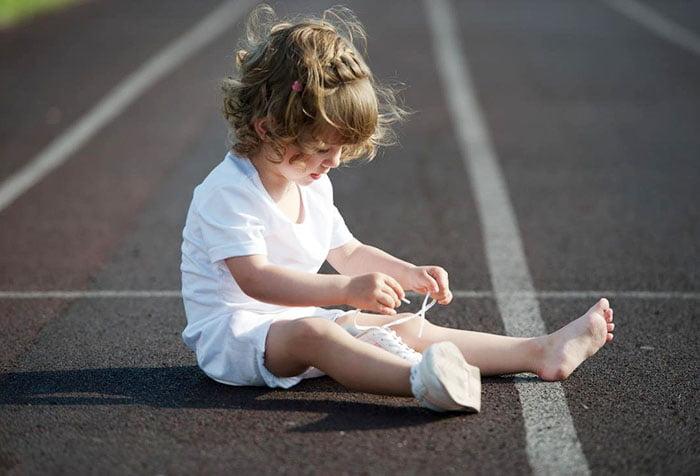Ребенок пытается завязать шнурки