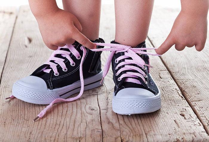 Малыш завязывает шнурки