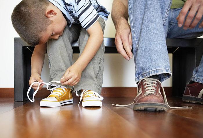 Мальчик завязывает шнурки перед прогулкой