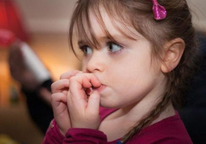 Девочка нервничает и грызет ногти