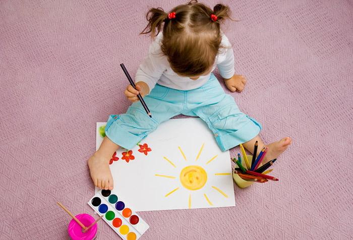 Девочка рисует, сидя на полу
