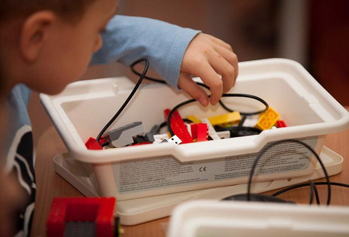 Ребенок разбирает детали для робота