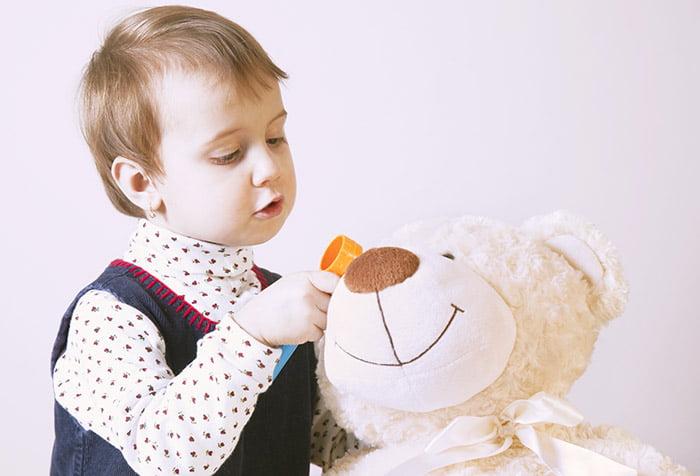 Ребенок играет с игрушечным медведем