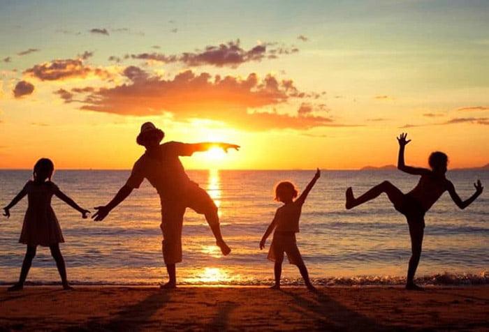 Семья с детьми играет у моря