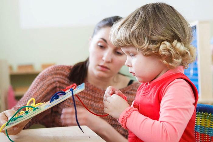 Мама показывает малышу игрушку со шнуровкой