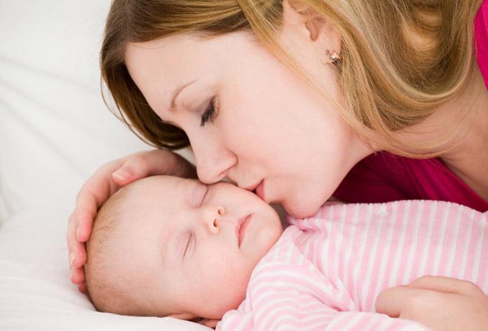 Мама целует спящего малыша