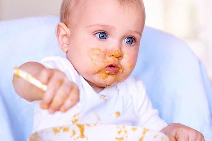 Малыш пытается есть самостоятельно