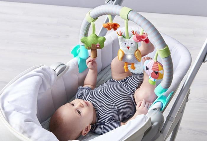 Малыш играет с мобилем в люльке