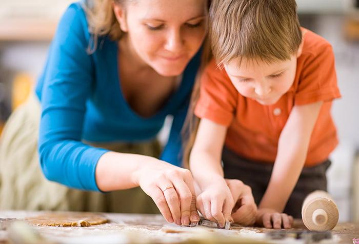 Мама с сыном вырезают фигурки из теста