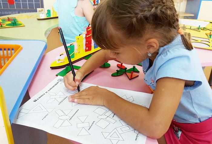 Девочка выполняет задание из сборника Воскобовича