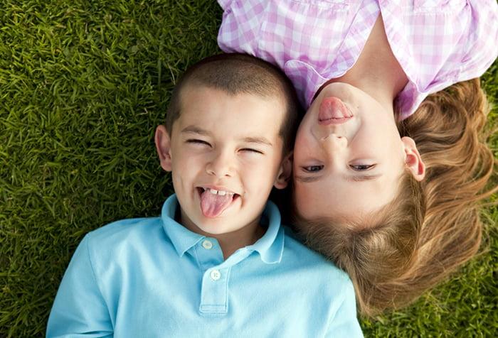Дети лежат на траве и дурачатся