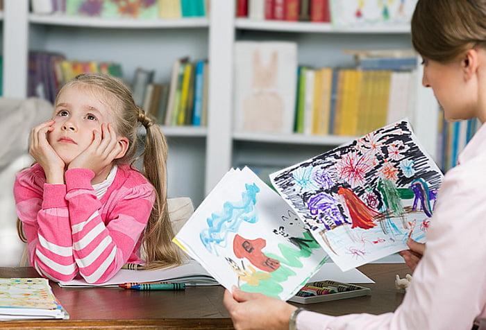 Психолог рассматривает рисунки девочки