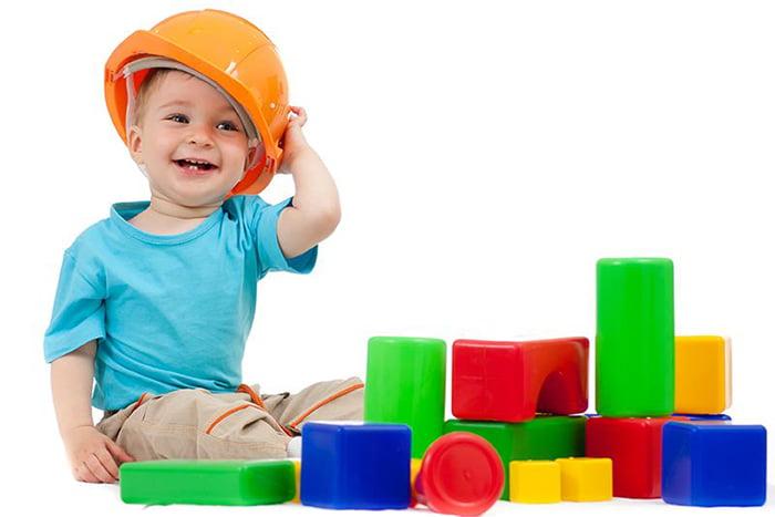 Малыш в каске с деталями конструктора
