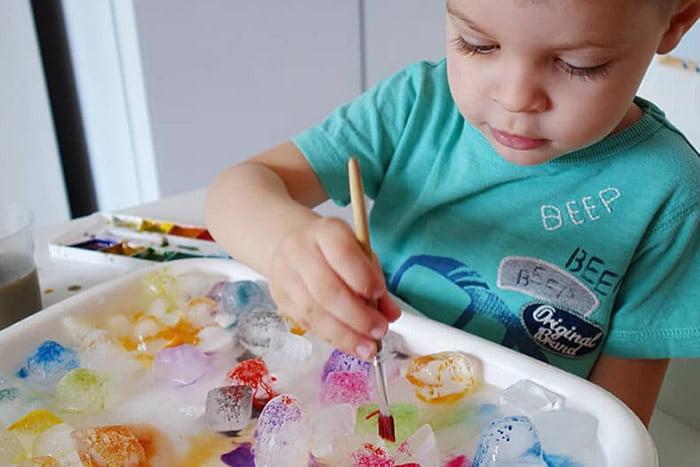 Ребенок красит кусочки льда