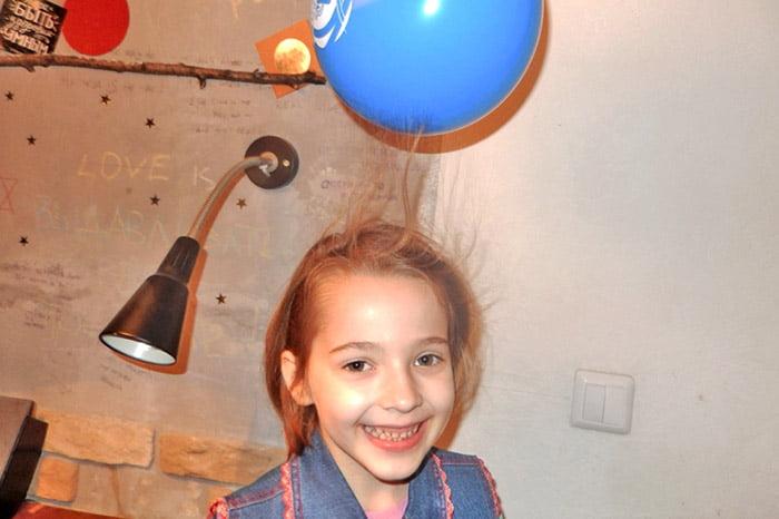 У девочки волосы прилипли к шарику