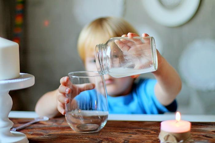 Ребенок переливает воду
