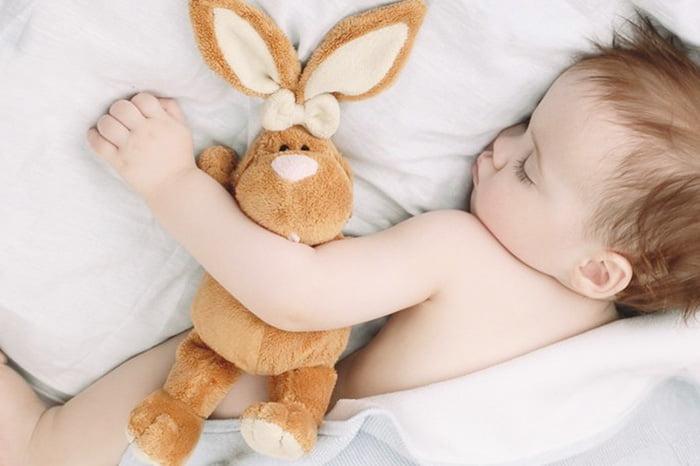 Годовалый ребенок спит с плюшевым зайцем