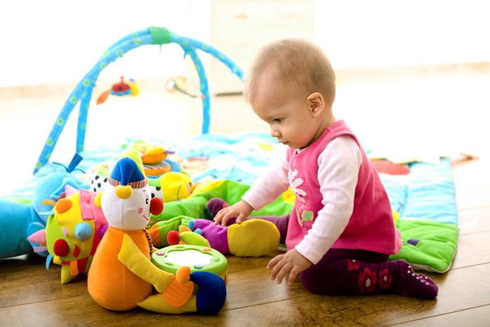 Маленькая девочка играет с мягкими игрушками