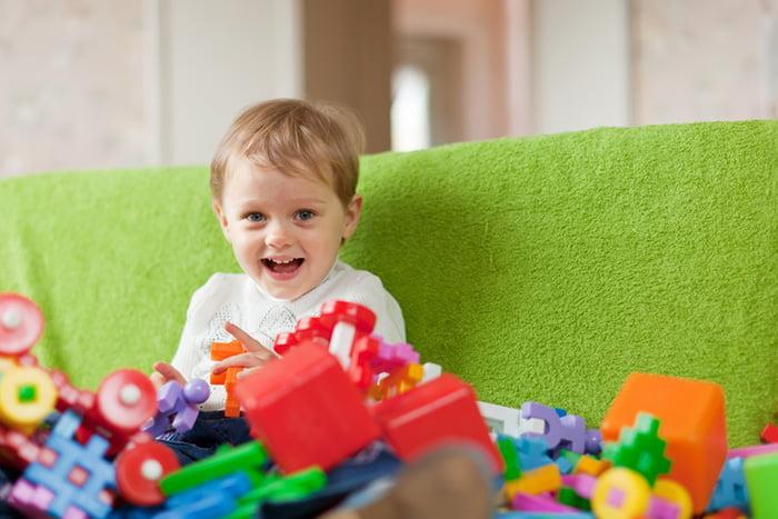 Ребенок на диване с кучей игрушек