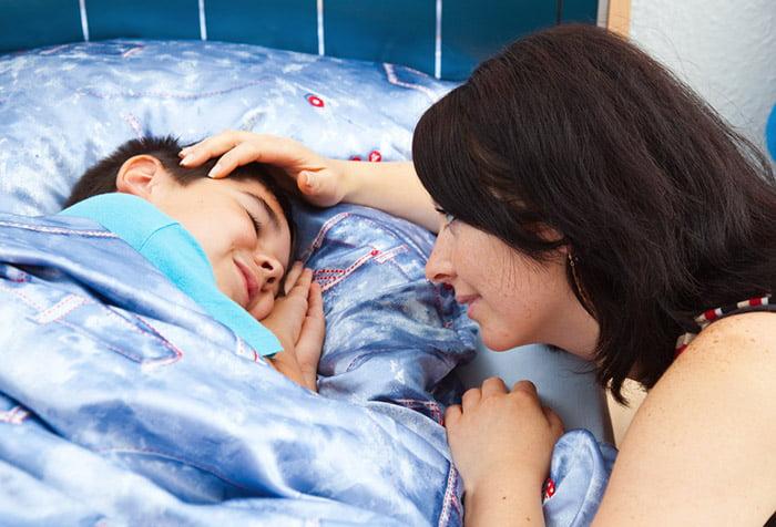 Мама гладит по голове спящего ребенка