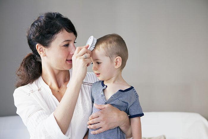 Мама причесывает ребенка
