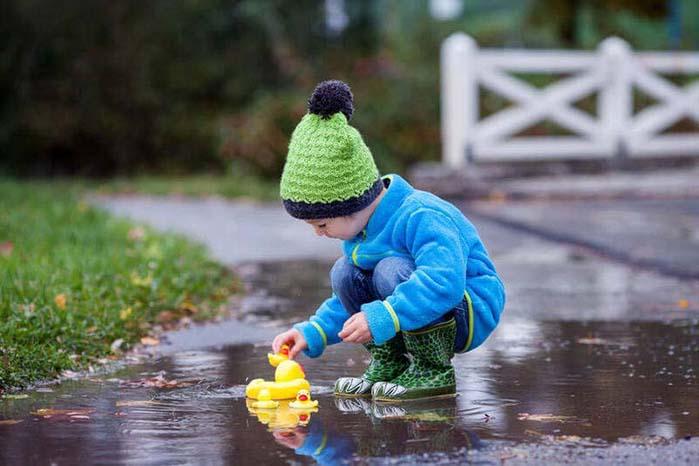 Ребенок играет в луже