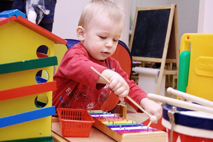 Ребенок с детским ксилофоном