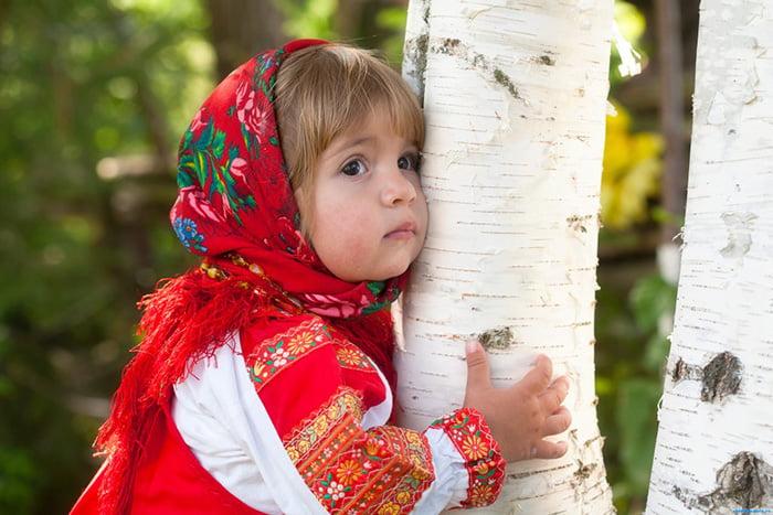 Девочка в народном костюме обнимает березу