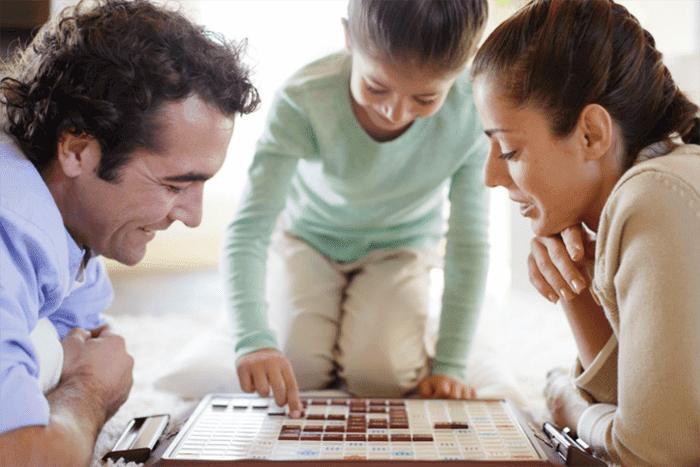 Девочка играет с родителями в настольную игру