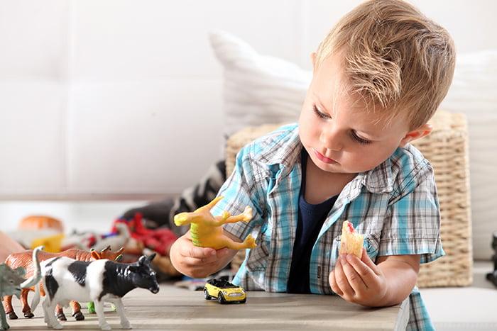 Ребенок играет с фигурками динозавров