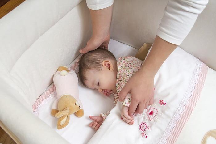 Малышка спит в своей кроватке