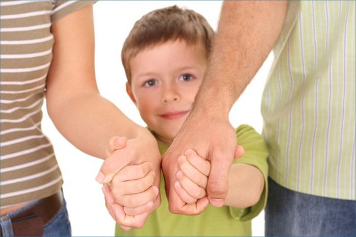 Ребенок держит родителей за руки