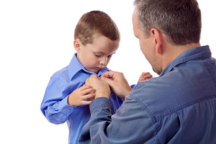 Папа помогает сыну застегнуть рубашку