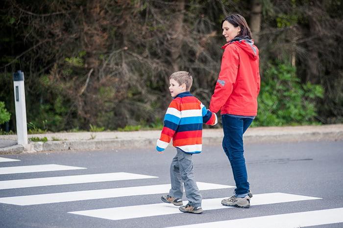 Мама с сыном переходят дорогу